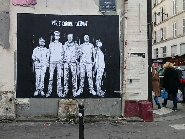 Auf einem Graffiti stehen Menschen unter einem Schriftzug.