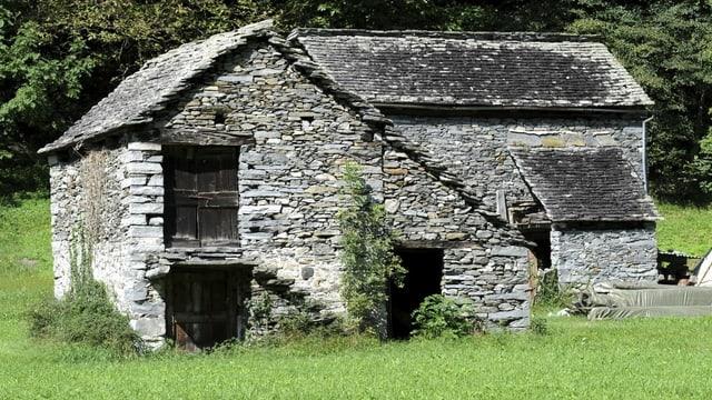 Ein Steinhaus steht in einer Wiese.