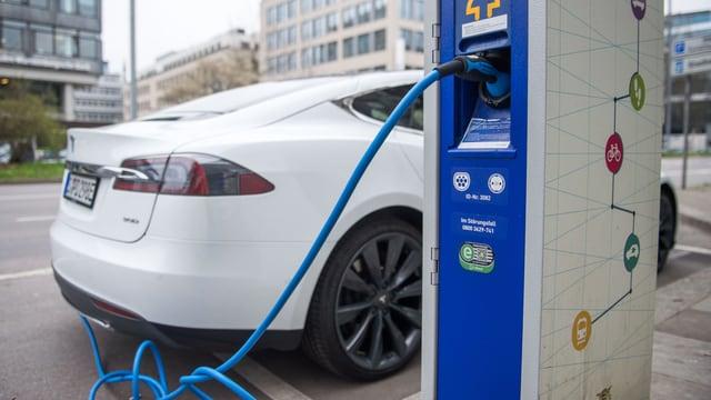 Ein weisses Auto wird an der Zapfsäule mit Strom betankt.
