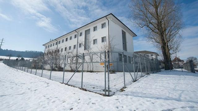 Gebäude der Strafanstalt Hindelbank im Schnee mit Zaun um das Gelände.