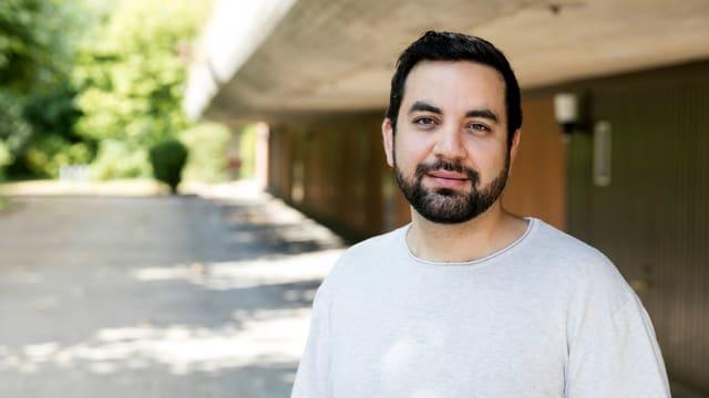 Ein junger Mann mit dunklen Haaren und Bart steht vor einem Gebäude.