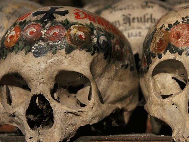Mit Rosenornamenten, Namen und Kreuzen verzierte Schädel.