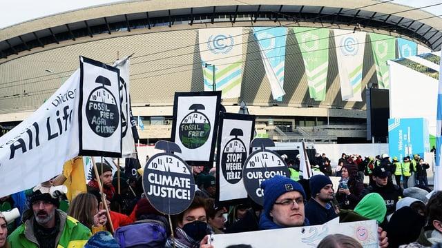 Demonstrierende halten Plakate hoch vor einem Gebäude.