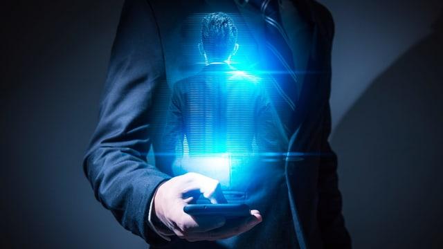 Ein Mann hält ein Smartphone in der Hand, vor ihm erscheint eine Projektion seiner selbst.