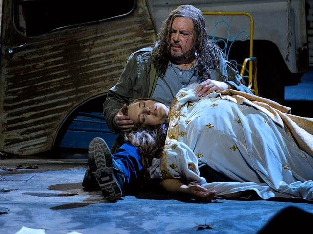 Mann mit langen Haaren und zerzausten Kleidern sitzt mit ausgestreckten Beinen auf dem Boden. In seinem Schoss liegt der Kopf einer jungen Frau.