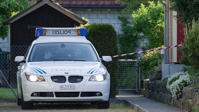 Polizeiauto in Hauseinfahrt, der mit Polizeiband abgesperrt ist