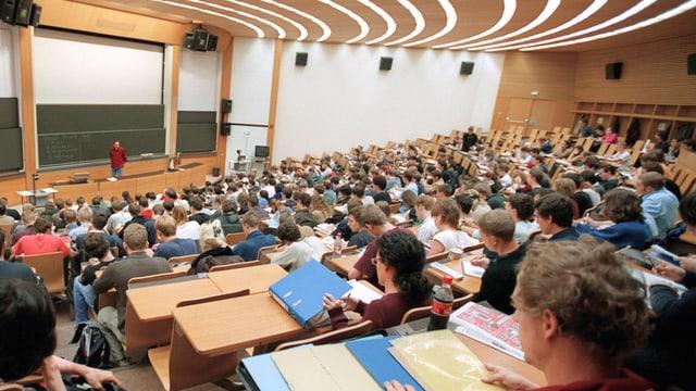 Ein Hörsaal der ETH Zürich, steil gegen unten. Man sieht viele Hinterköpfe der Studenten, die in den Bänken sitzen.