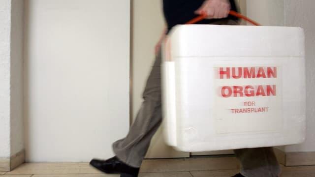 Ein Person trägt einen Koffer mit der Aufschrift menschliches Organ.