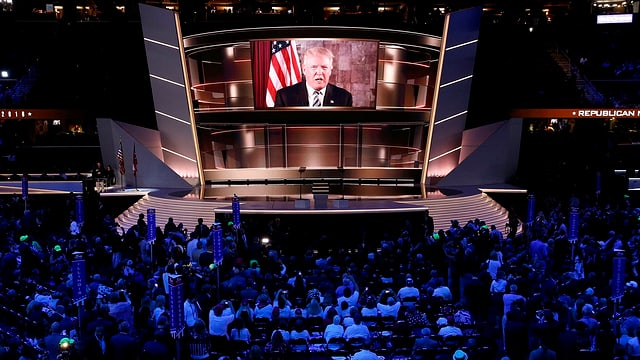 Menschen schauen auf eine Leinwand, auf der Donald Trump zu sehen ist.