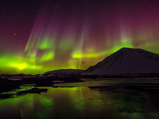 Im Vordergrund eine dunkle Nachtlandschaft mit einem schneebedeckten Berg. Am Himmel hat es grüne und violette Schleier - Polarlichter.
