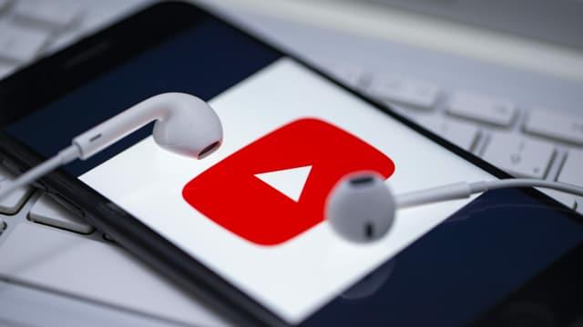 ein Handy mit einem YouTube-Logo und Kopfhörern