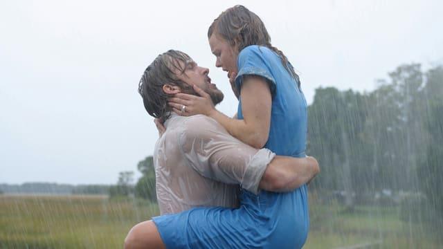 Mann mit langen Haaren und durchnässtem weissen Hemd küsst blonde Frau in blauem Kleid im Regen.