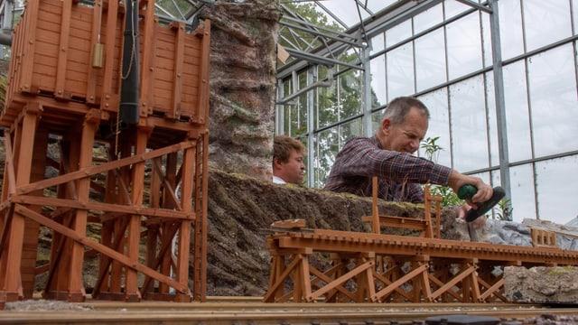 Modellbauer arbeitet an seiner Gartenbahn
