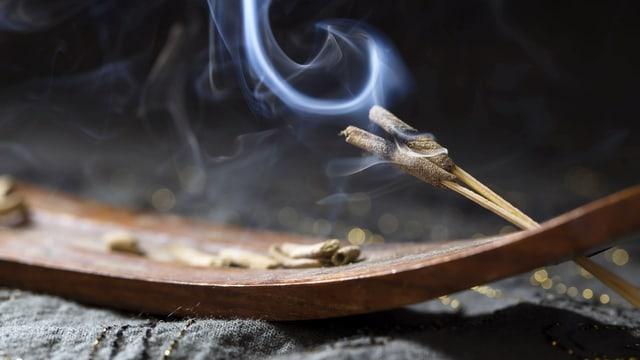 Zwei brennende Räucherstäbchen in einer hölzernen Halterung
