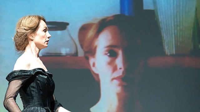 Ursina Lardi auf der Bühne in einem schwarzen Kleid. Im Hintergrund, projiziert, ist ihr Gesicht gross zu sehen.