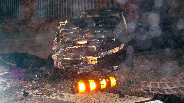 Zerstörtes schwarzes Auto mit umgekippter noch leuchtendem Verkehrszeichen im Vordergrund.
