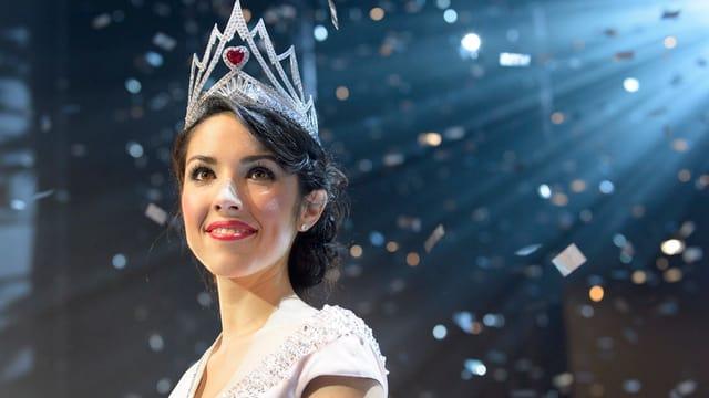 Die Miss Schweiz mit Krone und Glitterkofetti im Hintergrund.