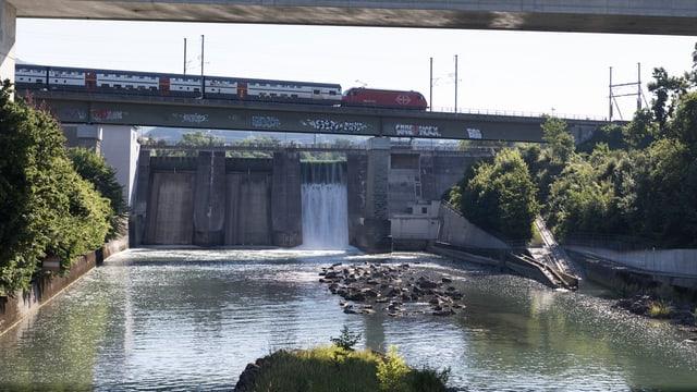 Ein Flusskraftwerk. Eine Eisenbahn fährt darüber.