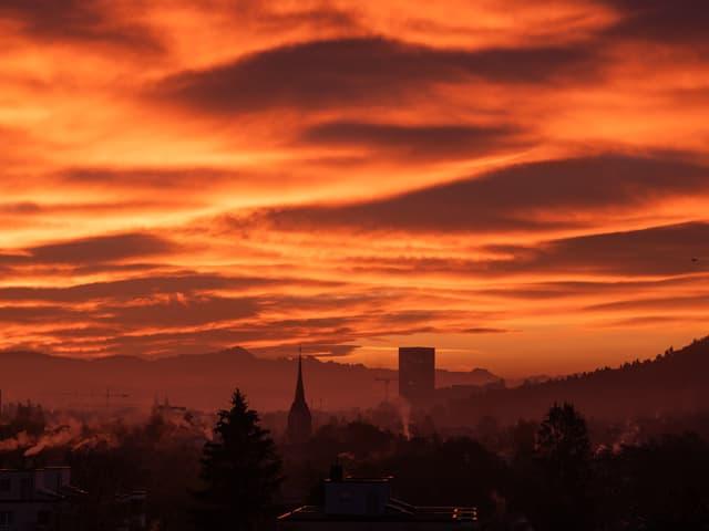 Rot-Orange Wolken am Himmel über einer Stadt.