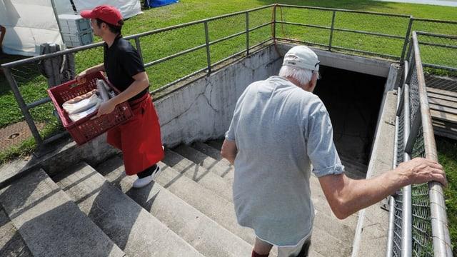 Ein junger Mann mit roter Kappe und Schürtze trägt eine Kiste die Treppe hoch, ein alter Mann geht die Treppe runter.