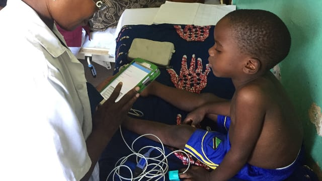 Dr. Samaka dal Ifakara Health Institute, examinescha in uffant cun il e-POCT.