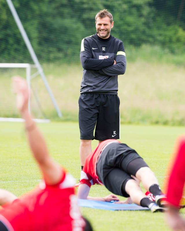 Sven Christ lachend und stehend, im Vordergrund Spieler bei Bodenübungen.