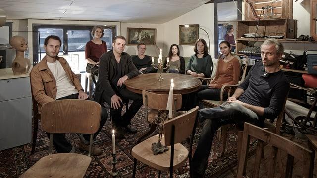 Die acht Musiker der Band Rudi Hayden in einem möblierten Zimmer.