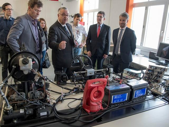 Männer in einem Raum mit Computern, Kabel und Autobatterien