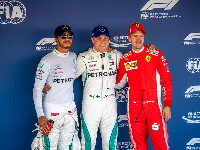 Valtteri Bottas (en mez), Lewis Hamilton (sanester) e Sebastian Vettel (dretg).