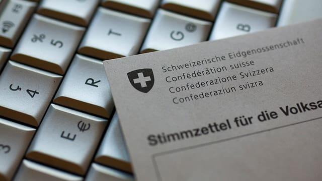 Man sieht eine Computertastatur und einen Stimmzettel einer Volksabstimmung