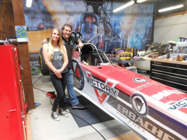 Vater und Tochter posieren vor ihrem Dragster-Rennwagen