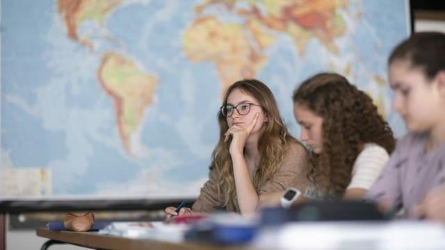 Drei junge Frauen sitzen bei einer Prüfung vor einer Weltkarte.