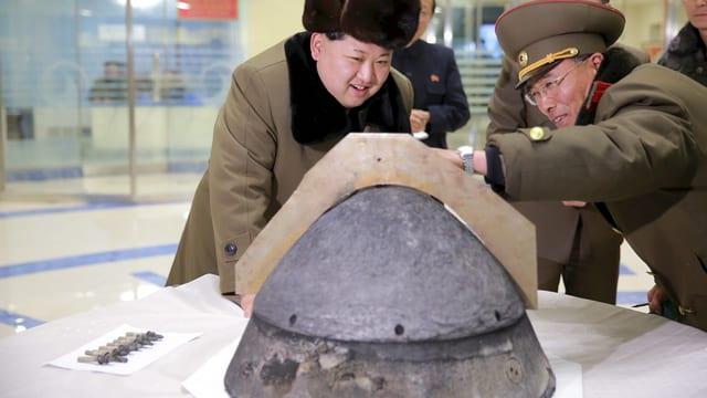Kim Jong Un begutachtet zusammen mit einem Militär einen Raketensprengkopf auf einem Tisch