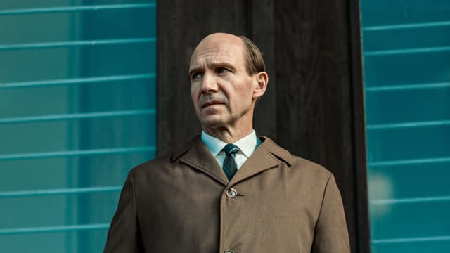 Ein Mann mit Halbglatze trägt ein Krawatte und einen Mantel und blickt ernst auf die Seite.
