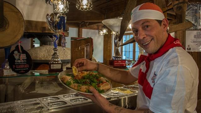 Claudio Vicanò en la pizzaria dal Catrina Ressort, nua ch'era ils pucals gudagnads fan parada.
