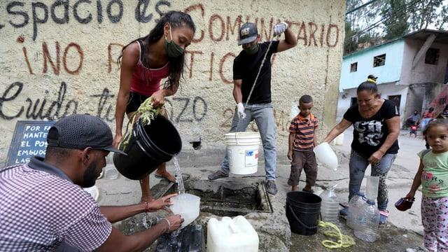 Frauen und Männer füllen an einer Wasserstelle ihre Plastikkanister auf.
