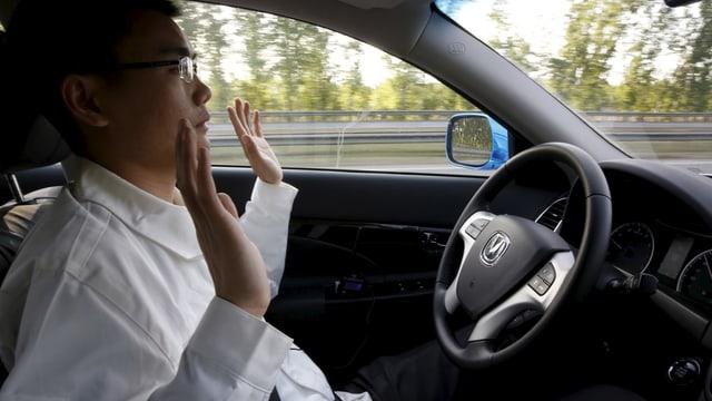 Mann im Auto, Hände vom Steuer weggenommen