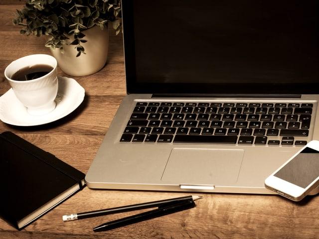 Auf einem Holztisch: Ein Notebook, ein Notizbuch, Stifte und eine Tasse Kaffee.