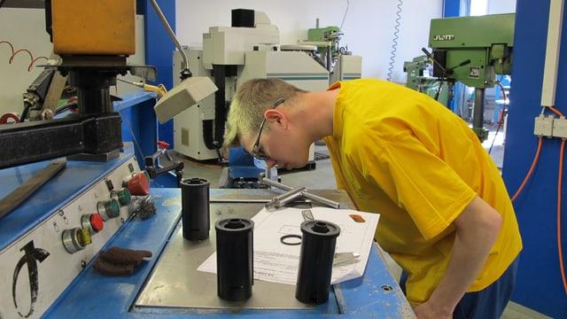 Junger Mann an einer Maschine, konzertrierte Arbeit