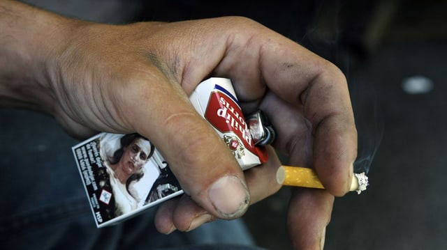 Maun che tegna ina cigaretta.