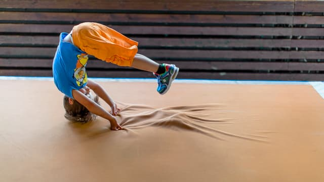 Kind macht einen Purzelbaum auf einer Matte.
