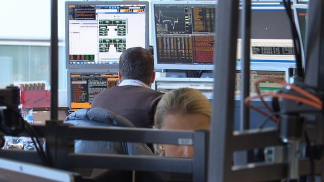 Mann vor mehreren Bildschirmen mit Grafiken und Kurven.