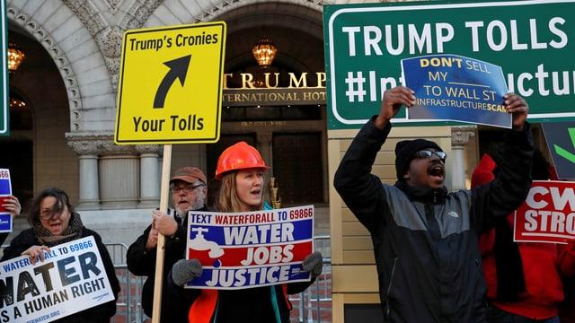 Protestler halten Plakate hoch.