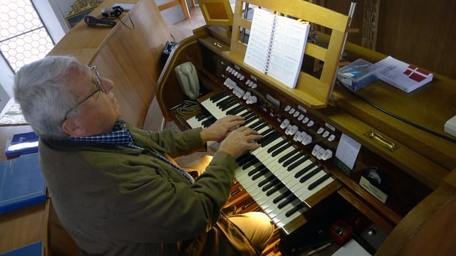 Mann spielt Orgel.