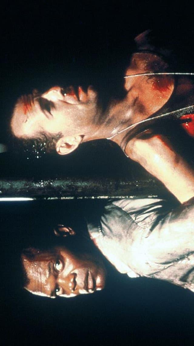 Zwei Schauspieler sind an einen Pfosten gefesselt.