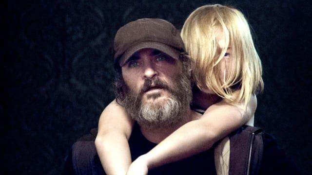 Ein bärtiger Mann mit Kappe trägt auf seinen Schultern ein blondes Mädchen