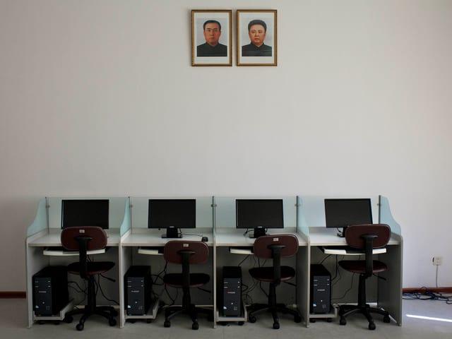 Vier leere Arbeitsplätze: Pulte mit je einem PC und einem Bildschirm und einem spartanischen Bürostuhl.
