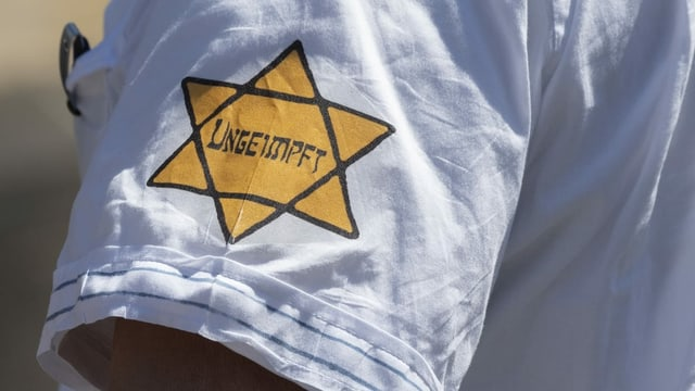 Ein nachgebildeter Judenstern auf einem Arm eines Protestierenden gegen Corona-Massnahmen.