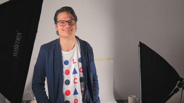 Dylan Blau steht vor einer weissen Wand zwischen zwei Scheinwerfern in seinem mobilen Studio.