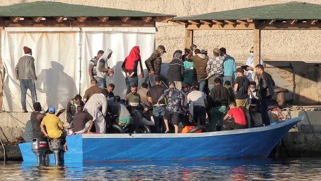 Boot mit jungen Männern legt an.